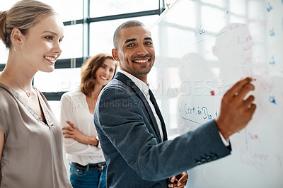 Buy stock photo Portrait of a young businessman brainstorming on a whiteboard with his colleagues in an office