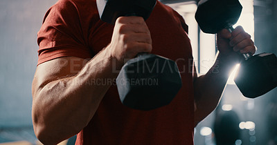 Buy stock photo Cropped shot of a man working out with dumbbells at the gym