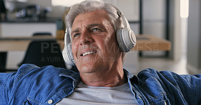 Buy stock photo Shot of a mature man sitting alone on the sofa at home and listening to music through headphones