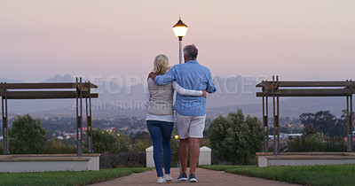 Buy stock photo Full length shot of a mature couple walking outside together with their arms around each other