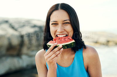 Buy stock photo Shot of a young woman eating a slice of watermelon on the beach