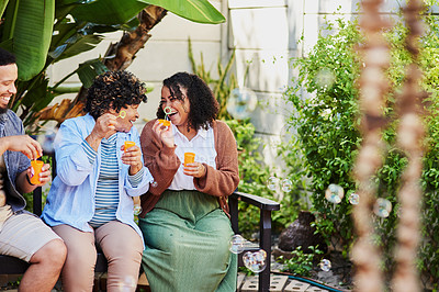 Buy stock photo Shot of a young man and woman blowing bubbles with their elderly relative in a garden
