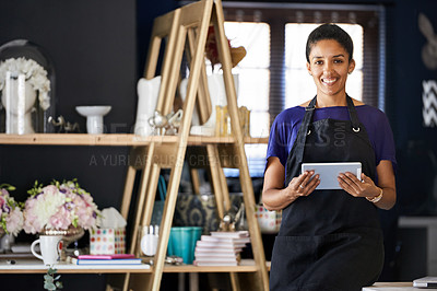 Buy stock photo Cropped portrait of an attractive young woman using a tablet while working in her flower shop
