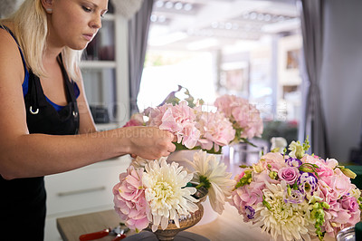Buy stock photo Shot of a young woman arranging the flowers at her job in a floral store