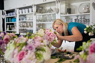 Buy stock photo Shot of a young woman pruning the flowers at her job in a floral store