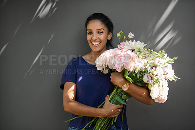 Buy stock photo Shot of a young woman posing with a bunch of flowers against a grey background