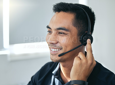 Buy stock photo Shot of a handsome young salesman sitting alone in his office and wearing a headset
