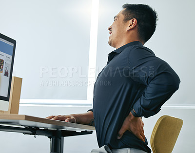 Buy stock photo Shot of a handsome young businessman sitting alone in his office and suffering from back ache