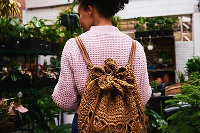 Buy stock photo Shot of a woman walking through a plant nursery