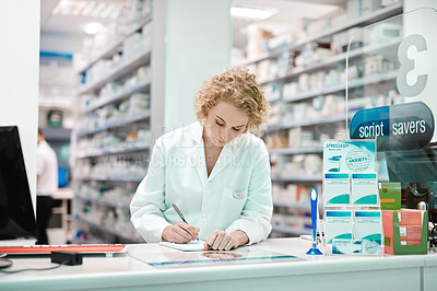 Buy stock photo Cropped shot of an attractive young female pharmacist working in a drugstore