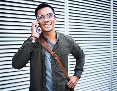 Buy stock photo Shot of a young man using a phone in the city