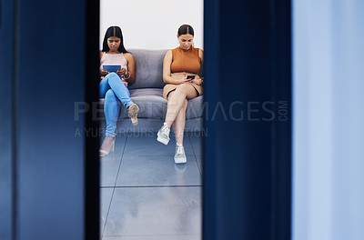 Buy stock photo Shot of two young women using their devices while waiting to be interviewed in a modern office