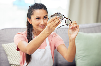 Buy stock photo Shot of a young woman cleaning her glasses while sitting at home