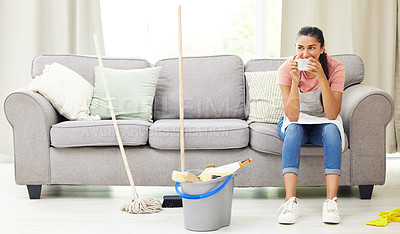 Buy stock photo Shot of a woman taking a coffee break while cleaning at home