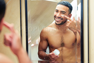 Buy stock photo Shot of a handsome young man looking in the mirror while applying moisturiser to his face