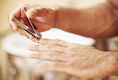 Buy stock photo Cropped shot of an unrecognizable man cutting his fingernails