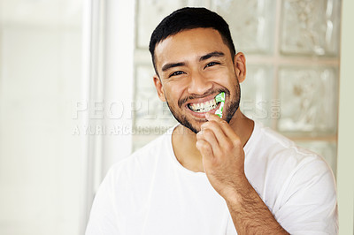Buy stock photo Shot of a handsome young man brushing his teeth at home