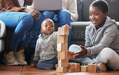 Buy stock photo Shot of a sister helping her baby brother build blocks in the lounge at home