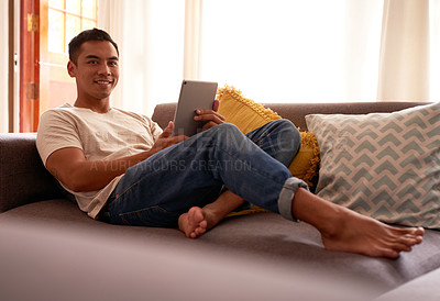 Buy stock photo Shot of a handsome young man sitting in his living room and using a digital tablet to work from home
