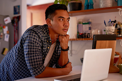 Buy stock photo Shot of a handsome young man standing alone at his kitchen counter and using his laptop to work from home