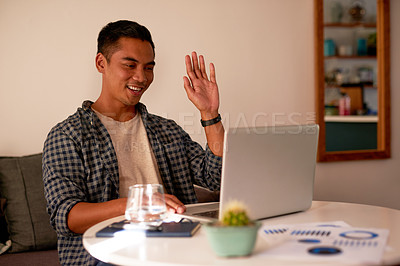 Buy stock photo Shot of a handsome young man sitting alone at home and using his laptop for a video call