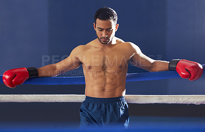 Buy stock photo Cropped shot of a handsome young male boxer leaning against the ropes during a fight in the ring