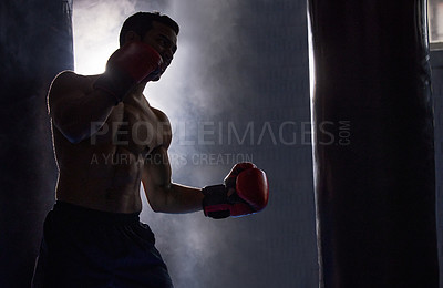Buy stock photo Cropped shot of a silhouetted young male boxer working out on a punching bag in the gym