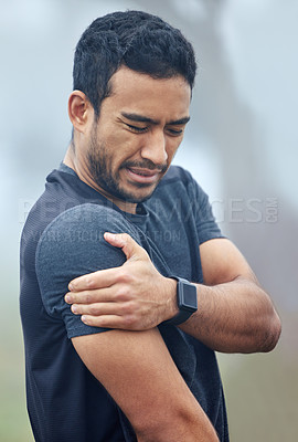 Buy stock photo Shot of a sporty young man holding his shoulder in pain while exercising outdoors