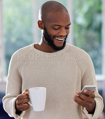 Buy stock photo Shot of a young man drinking coffee while using a phone at home