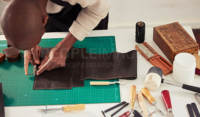Buy stock photo High angle shot of an unrecognizable male designer working with leather in his design studio