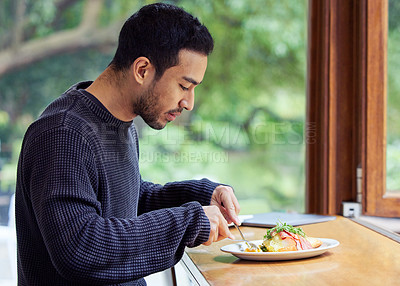 Buy stock photo Shot of a man enjoying a plate of food in a cafe