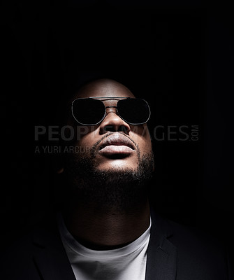 Buy stock photo Studio shot of a man wearing sunglasses while posing against a dark background