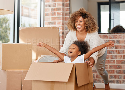 Buy stock photo shot of a mother pushing her daughter in a box at home