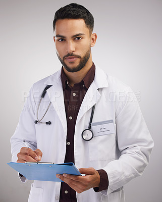 Buy stock photo Shot of a handsome young doctor standing alone in the studio and writing on a clipboard