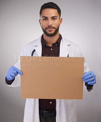 Buy stock photo Shot of a handsome young doctor standing alone in the studio and holding up a poster