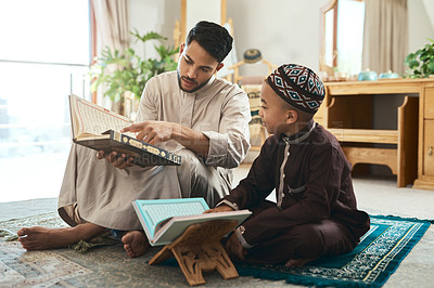 Buy stock photo Shot of a young muslim man and his son reading in the lounge at home