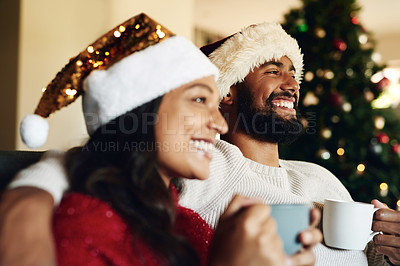 Buy stock photo Shot of a happy young couple relaxing on the sofa and having warm drinks during Christmas at home