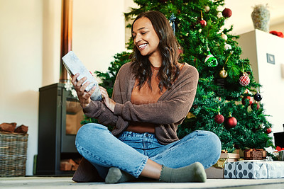Buy stock photo Shot of a happy young woman opening presents during Christmas at home
