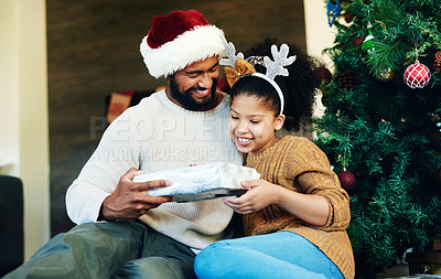 Buy stock photo Shot of a cute little girl opening presents with her father during Christmas at home