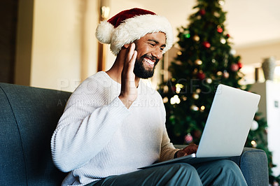 Buy stock photo Shot of a happy young man using a laptop to make a video call during Christmas at home