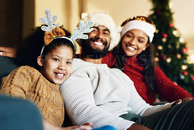 Buy stock photo Shot of a happy young family relaxing on the sofa during Christmas at home