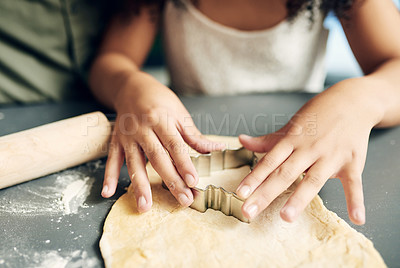 Buy stock photo Shot of an unrecognisable little girl making cookies with her parent during Christmas at home