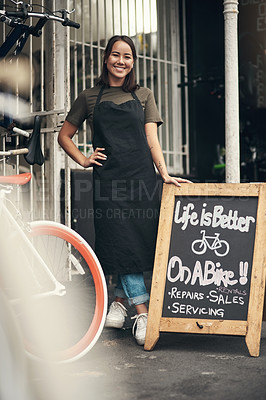 Buy stock photo Full length shot of an attractive young woman standing outside her bicycle shop during the day