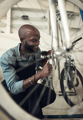 Buy stock photo Shot of a handsome young man crouching alone in his shop and repairing a bicycle wheel