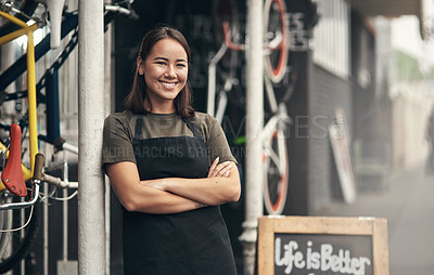Buy stock photo Shot of an attractive young woman standing outside her bicycle shop with her arms folded
