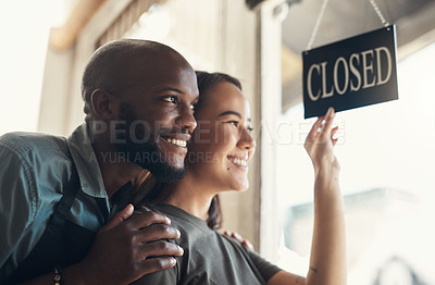 Buy stock photo Shot of a young couple standing together and turning the sign on the door to their bicycle shop