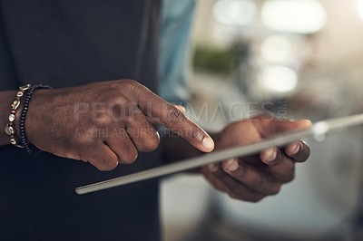 Buy stock photo Cropped shot of an unrecognizable man standing alone in his bicycle shop and using a digital tablet