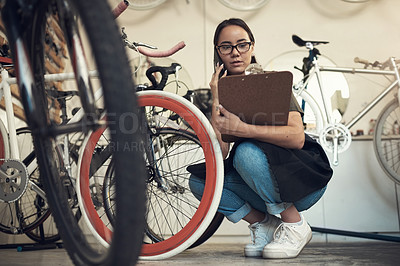 Buy stock photo Full length shot of an attractive young woman crouching in her bicycle shop and using her cellphone while holding a clipboard
