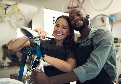 Buy stock photo Shot of a young couple standing together in their bicycle shop during the day