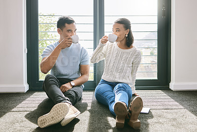 Buy stock photo Full length of a young couple sitting together in their new home and enjoying a cup of tea